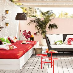A simple wooden construction creates a low sofa come daybed and topped with a foam seat pad in a bright zingy tomato-red fabric