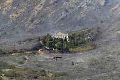 Fire burned around a house as a helicopter returns from dropping water on the Quail Fire in Alpine, Utah, July 3, 2012.