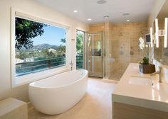 A stylish freestanding bathtub is strategically placed under an oversized picture window offering spectacular views from this chic, contemporary bathroom in the Hollywood Hills. Floors made of limestone and cabinetry made of rift cut oak creates a spa-like atmosphere. The shower, with mosaic multi-toned marble, is designed to be romantically occupied by two.