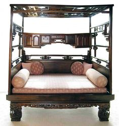 An extraordinary 19th century solid nan wood carved and mortise and tenon constructed opium bed featuring rotating hangers on each side wall, and a cabinet below the canopy top with drawers