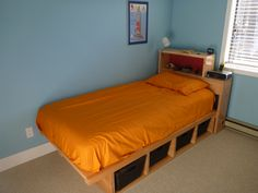 single child's bed with storage underneath. Headboard is for books etc. Designed, created and made by Chris Ellsay.