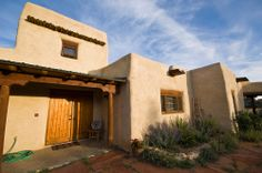 This adobe Pueblo style house in New Mexico has vigas, a flat roof with a rain spout, a porch supported with zapatas, and a heavy wooden door. Pueblo House, American Home Design, Mission Style Homes, Revival Architecture, Residential Architecture, Mexico House, Adobe House, Santa Fe Style, Hacienda Style