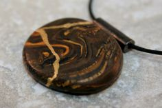 Kintsugi (or kintsukuroi) style circle pendant in a swirled mix of browns and gold polymer clay with gold repair - OOAK by AKintsugiLife