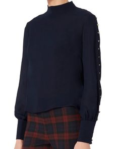 Exclusive for Intermix Candice Button Blouse: Gold-tone buttons along the length of the long sleeves. Slit back hem. Back zip closure. Sheer. In navy. Fabric: 100% silk Made in China   Model Measurements: Height 5'8.5 ; Waist 24 ; Bust 33 wearing size S  Length from shoulder to hem: ...