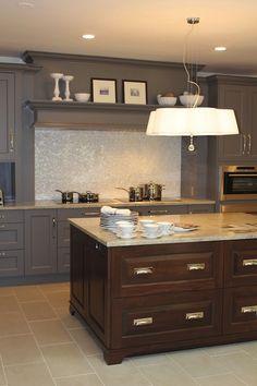 source: Aidan Design Two-tone kitchen design with gray kitchen cabinets, chocolate brown kitchen island, granite countertops, mosaic glass tiles backsplash and white chandelier.
