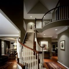 Love the dark wood floors with white wood balusters and dark railing. Warm taupe color on walls with recessed lighting. Perfect.