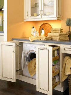 Subtly Sophisticated  Kraftmaid semi-custom maple cabinetry in an Irish Cream finish adapts to the laundry room with bifold doors that hide the appliances and a 12-inch pantry-style pullout that stores laundry supplies. Open storage under the counter accommodates laundry baskets or wheelchair access.