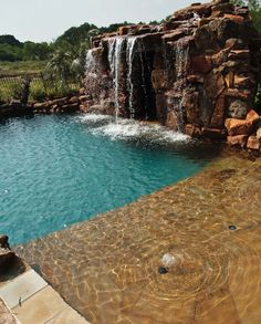 Residential swimming pool with beach entry and waterfall by Water Wizard Pools