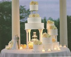 This romantic wedding cake has 6 tiers - but 4 of them are separate and off to the side. A lighted water fountain was placed under the base and candles were use to give it romantic lighting. Notice one of the offset cakes is also a tiered wedding cake.