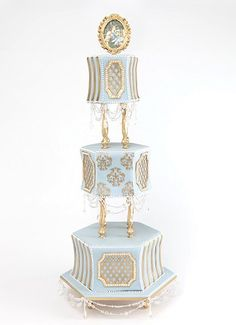 """Custom gold pillars divide carved, blue tiers with gilded detailing; """"chandelier"""" beading and an edible rendition of J. Spencer Stanhope's Love and the Maiden complete the look. By Elizabeth Hodes Custom Cakes and Sugar Art. Pretty Wedding Cakes, Amazing Wedding Cakes, Wedding Cake Designs, Pretty Cakes, Amazing Cakes, Wedding Themes, Wedding Ideas, Victorian Wedding Cakes, Victorian Cakes"""