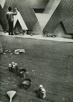 """Della serie """"fotografie di artisti al lavoro"""", ecco una bellissima istantanea di Frank Stella che dipinge nel suo studio."""