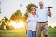 portrait of happy senior couple playing golf enjoying retirement by JoshuaResnick