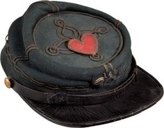 """148th New York Civil War Officer's Kepi. Fine quality blue wool body with two bands of black quatrefoil on the crown, along with two bands at the front, back, and sides, and around the base of the crown. Stitched on the crown is a flat gold bullion bordered 1st Division 24th Corps Badge. The hat retains the original 1 5/8"""" wool backed, gold bullion and brass sequin officer's infantry horn insignia with separately affixed false embroidered silvered numbers """"148"""" above."""