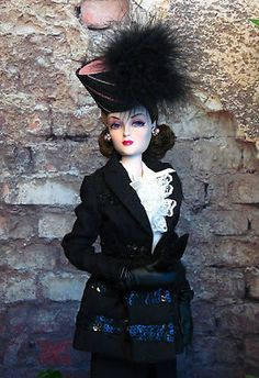 "American film star, Miss Zita Charles shows her support for the brave women of Paris by wearing a fabulously dramatic hat from The Couture Touch.  The black wool suit with sequin trim is from Robert Tonner's Theatre de la Mode collection, Le Petit Ensemble Noir.  Lace trimmed blouse is from Ashton Drake's ""Blonde Lace"", leathette gloves from Integrity, purse from Madame Alexander, and earrings from The Couture Touch.  A restyled City Sleeker Zita Charles is from Integrity."