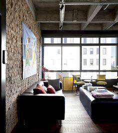 Sala de estar: sofá e banco da Etna, renovados com couro preto. Almofadas da Art Maison. Na parede, gravura em lona de Gustavo Rosa. Apoiado no chão, quadro amarelo da Loja Teo (Foto: Marco Antonio/Editora Globo)