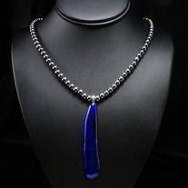 Prismatic blue, rich grey and deep black glisten and reflect a mysterious dynamism that only a few catch glimpses into. This elongated dichroic glass pendant beholds a prestige of its own and is centered within a chromatic string of hematite spheres. One-of-a-kind and echoing an awareness of dept...
