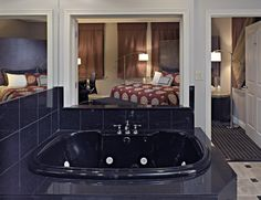 Oversized fully marble bathroom with Jacuzzi tub and separate glass shower in the VIP Suite at the Madison Hotel in Memphis.