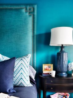 A bright blue bedroom is dominated by a dramatic teal upholstered headboard. Pillows in assorted shades of blue add a cozy layer to the bedding.