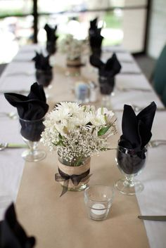 Kraft paper table runners, black napkins, white flowers in mason jars with burlap and black ties