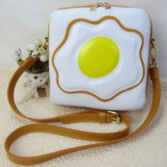 Kawaii fried egg cross shoulder bag with zip closure, inside pockets and adjustable strap.  Also features plush white background.