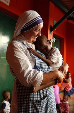 A nun cuddling an orphan in Mozambique. Photographer: Mick Yates.  Bless those wonderful women.