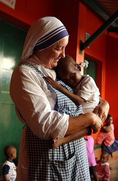 A nun cuddling an orphan in Mozambique. Photographer: Mick Yates  Don't you just love how the Catholic Church is this big monolithic mean ogre?