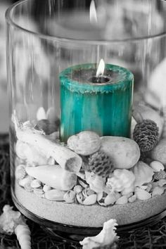 The candle which is lit up is a turquoise color while its surrounded by white shells in a clear vase