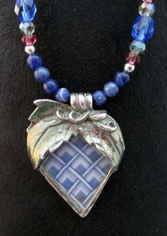 Fine silver and old china combine for this heart pendant. Love