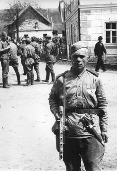The Red Army soldier posing in a Czech village just liberated is also carrying a captured German dagger, 1945.