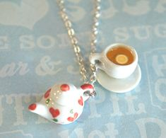 """This necklace features a miniature ceramic teapot pendant along with a lemon tea cup charm. Both hangs on a silver tone chain necklace that measures 24"""" in length. SKU 1559"""