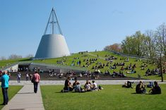 TU Delft Library, South Holland, Netherlands. The roof of the library is covered with grass, which serves as a natural insulation. The structure lifts from the ground on one side allowing to walk to the top of the building. The library is topped by the steel cone, giving its unique shape. The wall, opposite to the Aula is completely filled with glass.
