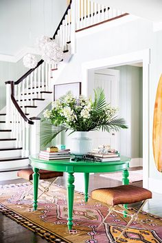A vibrant green circular table in a white entranceway