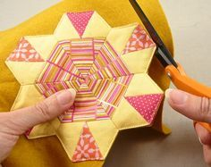 Learn the fine art of English Paper Piecing with this free downloadable pattern and tutorial. Make a simple flower shaped coaster with hexagons.