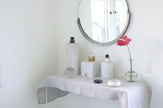 Great idea for an inexpensive vanity: CB2 peekaboo table, linen tea towel, a sunny corner. Design by Sophie Buhai