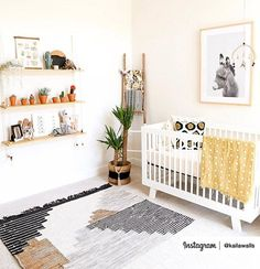 Adorable nursery with white crib, grey and white rug, yellow blanket