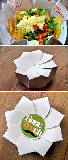 Este envase está diseñado para las comidas rápidas de Guactruck, en Manila, Philippines. Inspirado en la cultura del origami, la comida emerge de una flor recién abierta. Está diseñado en una sola pieza sin utilizar plástico ni pegamentos, solo el plegado. Diseñado por Michealle Lee.