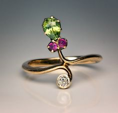 Art Nouveau Gemstone Flower Ring made in St Petersburg between 1899 and 1904 A 14K gold ring is set with a drop shaped sparkling green demantoid garnet (5.
