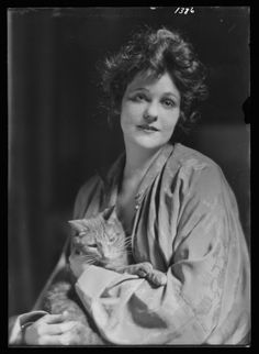 A woman holding Buzzer the cat (photo by Arnold Genthe)