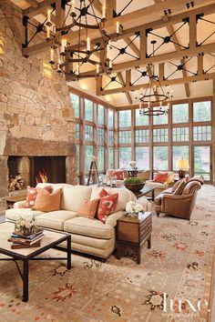 Two Hancock & Moore sofas, placed back to back, are covered with fabric from Cowtan & Tout, and chandeliers from Paul Ferrante hang above. T...