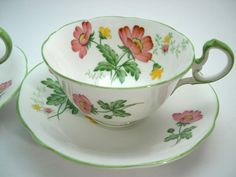 This is for 2 tea cups and saucers made by Aynsley, England  White tea cup set with pink and yellow flowers.  The backstamp date these cups to 1926 - 1934  The rims and thumbrest are green.  Cup Measures: 2 1/8 high & Saucer Measures 5 5/8 diameter  Very good conditon, no chips, no cracks, no hairline and both pieces ring nicely.  These items are quite old and I am trying to describe them the best that I can and to show the imperfections on the pictures.