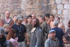 Game of Thrones: On the set. The hound is smiling! And surrounded by modern people in King's Landing.