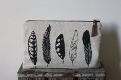This feather print was hand drawn and screen printed in a black solvent free ink the exterior fabric is an 100% natural coloured linen the lining fabric is an 100% cotton canvas this pouch features a brass zipper and a leather zipper pull reinforced with a brass rivet approx. dimensions
