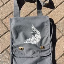 Hand painted 14 oz. Pigment-Dyed Canvas Field Bag with a Peacock  design on it. Color of this bag is smoke grey. Design is painted in white on front flap only. Perfect for conventions, trips to the comic shop, as a reusable shopping bag or as a purse.      Color: Smoke grey     100% cotton can...