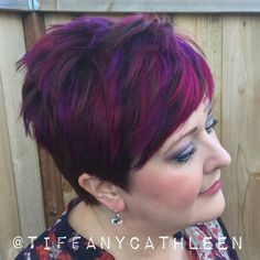Pixie cut with magenta and violet balayage highlights.