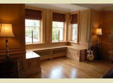 A Hallidays polished pine window seating with built in radiator covers