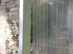 Metal coil curtain as door curtain divides room from outside.