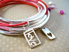 Set of 10 baby pink, deep pink and red leather bangle bracelets with silver tube beads. Perfect gift for your valentine of any age. Two sterling charms dangle the message of heart and love.