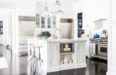 When blogger Sue De Chiara designed her Connecticut home, she wasn't about to do away with the nickel-trimmed pendants from the family's previous home. Instead, she kept them and went for the brass hardware she wanted, using some simple industrial stools and blue and white accents to tie the look together.