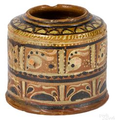 "Pook & Pook October. 3, 2015 Lot 102.  Estimated: $4000 - $7000.  Realized Price: $11,400.  Montgomery County, Pennsylvania redware canister, ca. 1800, with extensive yellow and brown slip decoration, 5 3/4"" h. Provenance: Delaware Estate."