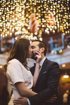 The wedding couple, bride and groom kissing under the Christmas lights in Faneuil Hall in Boston, Massachusetts | Wedding Photography